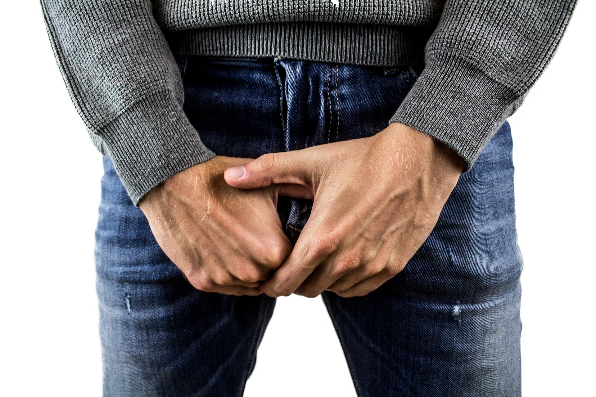 man holding his hands over his jeans